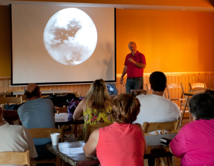 Photo: Lecturer with projected image of Saturn's moon Titan. Photo by James Guilford.