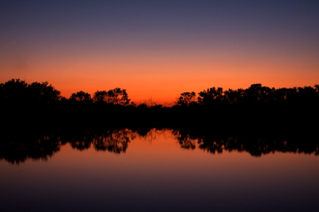 Photo: Sunset over the still lake at park. Photo by James Guilford.