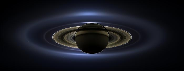 Photo: Planet Saturn, backlit. On July 19, 2013, in an event celebrated the world over, NASA's Cassini spacecraft slipped into Saturn's shadow and turned to image the planet, seven of its moons, its inner rings -- and, in the background, our home planet, Earth. With the sun's powerful and potentially damaging rays eclipsed by Saturn itself, Cassini's onboard cameras were able to take advantage of this unique viewing geometry. They acquired a panoramic mosaic of the Saturn system that allows scientists to see details in the rings and throughout the system as they are backlit by the sun. This mosaic is special as it marks the third time our home planet was imaged from the outer solar system; the second time it was imaged by Cassini from Saturn's orbit; and the first time ever that inhabitants of Earth were made aware in advance that their photo would be taken from such a great distance.  With both Cassini's wide-angle and narrow-angle cameras aimed at Saturn, Cassini was able to capture 323 images in just over four hours. This final mosaic uses 141 of those wide-angle images. Images taken using the red, green and blue spectral filters of the wide-angle camera were combined and mosaicked together to create this natural-color view. A brightened version with contrast and color enhanced (Figure 1), a version with just the planets annotated (Figure 2), and an annotated version (Figure 3) are shown above.  This image spans about 404,880 miles (651,591 kilometers) across.  The outermost ring shown here is Saturn's E ring, the core of which is situated about 149,000 miles (240,000 kilometers) from Saturn. The geysers erupting from the south polar terrain of the moon Enceladus supply the fine icy particles that comprise the E ring; diffraction by sunlight gives the ring its blue color. Enceladus (313 miles, or 504 kilometers, across) and the extended plume formed by its jets are visible, embedded in the E ring on the left side of the mosaic.  At the 12 o'clock position and a bit inward from the E ring lies the barely discernible ring created by the tiny, Cassini-discovered moon, Pallene (3 miles, or 4 kilometers, across). (For more on structures like Pallene's ring, see PIA08328). The next narrow and easily seen ring inward is the G ring. Interior to the G ring, near the 11 o'clock position, one can barely see the more diffuse ring created by the co-orbital moons, Janus (111 miles, or 179 kilometers, across) and Epimetheus (70 miles, or 113 kilometers, across). Farther inward, we see the very bright F ring closely encircling the main rings of Saturn.  Following the outermost E ring counter-clockwise from Enceladus, the moon Tethys (662 miles, or 1,066 kilometers, across) appears as a large yellow orb just outside of the E ring. Tethys is positioned on the illuminated side of Saturn; its icy surface is shining brightly from yellow sunlight reflected by Saturn. Continuing to about the 2 o'clock position is a dark pixel just outside of the G ring; this dark pixel is Saturn's Death Star moon, Mimas (246 miles, or 396 kilometers, across). Mimas appears, upon close inspection, as a very thin crescent because Cassini is looking mostly at its non-illuminated face.  The moons Prometheus, Pandora, Janus and Epimetheus are also visible in the mosaic near Saturn's bright narrow F ring. Prometheus (53 miles, or 86 kilometers, across) is visible as a faint black dot just inside the F ring and at the 9 o'clock position. On the opposite side of the rings, just outside the F ring, Pandora (50 miles, or 81 kilometers, across) can be seen as a bright white dot. Pandora and Prometheus are shepherd moons and gravitational interactions between the ring and the moons keep the F ring narrowly confined. At the 11 o'clock position in between the F ring and the G ring, Janus (111 miles, or 179 kilometers, across) appears as a faint black dot. Janus and Prometheus are dark for the same reason Mimas is mostly dark: we are looking at their non-illuminated sides in this mosaic. Midway between the F ring and the G ring, at about the 8 o'clock position, is a single bright pixel, Epimetheus. Looking more closely at Enceladus, Mimas and Tethys, especially in the brightened version of the mosaic, one can see these moons casting shadows through the E ring like a telephone pole might cast a shadow through a fog.  In the non-brightened version of the mosaic, one can see bright clumps of ring material orbiting within the Encke gap near the outer edge of the main rings and immediately to the lower left of the globe of Saturn. Also, in the dark B ring within the main rings, at the 9 o'clock position, one can see the faint outlines of two spoke features, first sighted by NASA's Voyager spacecraft in the early 1980s and extensively studied by Cassini.  Finally, in the lower right of the mosaic, in between the bright blue E ring and the faint but defined G ring, is the pale blue dot of our planet, Earth. Look closely and you can see the moon protruding from the Earth's lower right. (For a higher resolution view of the Earth and moon taken during this campaign, see PIA14949.) Earth's twin, Venus, appears as a bright white dot in the upper left quadrant of the mosaic, also between the G and E rings. Mars also appears as a faint red dot embedded in the outer edge of the E ring, above and to the left of Venus.  For ease of visibility, Earth, Venus, Mars, Enceladus, Epimetheus and Pandora were all brightened by a factor of eight and a half relative to Saturn. Tethys was brightened by a factor of four. In total, 809 background stars are visible and were brightened by a factor ranging from six, for the brightest stars, to 16, for the faintest. The faint outer rings (from the G ring to the E ring) were also brightened relative to the already bright main rings by factors ranging from two to eight, with the lower-phase-angle (and therefore fainter) regions of these rings brightened the most. The brightened version of the mosaic was further brightened and contrast-enhanced all over to accommodate print applications and a wide range of computer-screen viewing conditions.  Some ring features -- such as full rings traced out by tiny moons -- do not appear in this version of the mosaic because they require extreme computer enhancement, which would adversely affect the rest of the mosaic. This version was processed for balance and beauty.  This view looks toward the unlit side of the rings from about 17 degrees below the ring plane. Cassini was approximately 746,000 miles (1.2 million kilometers) from Saturn when the images in this mosaic were taken. Image scale on Saturn is about 45 miles (72 kilometers) per pixel.  This mosaic was made from pictures taken over a span of more than four hours while the planets, moons and stars were all moving relative to Cassini. Thus, due to spacecraft motion, these objects in the locations shown here were not in these specific places over the entire duration of the imaging campaign. Note also that Venus appears far from Earth, as does Mars, because they were on the opposite side of the sun from Earth.   Image Credit: NASA/JPL-Caltech/SSI