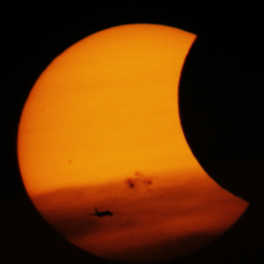 Photo: Partial Solar Eclipse with airplane. By Matt Franduto