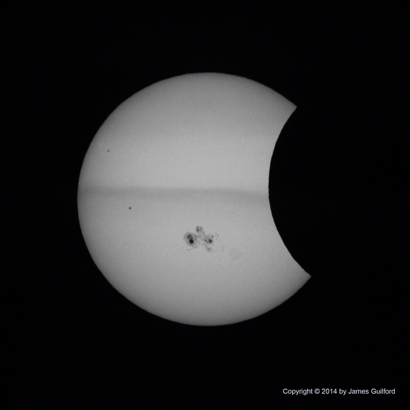 Streaks of Cloud and a Giant Sunspot Group Cross Sun's Face - Photo by James Guilford