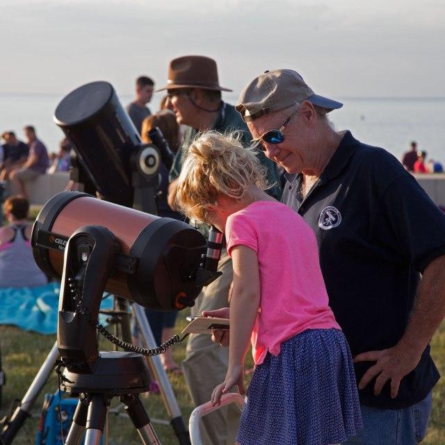 Photo: Girl views Sun through a CAA member's telescope. Photo by James Guilford.