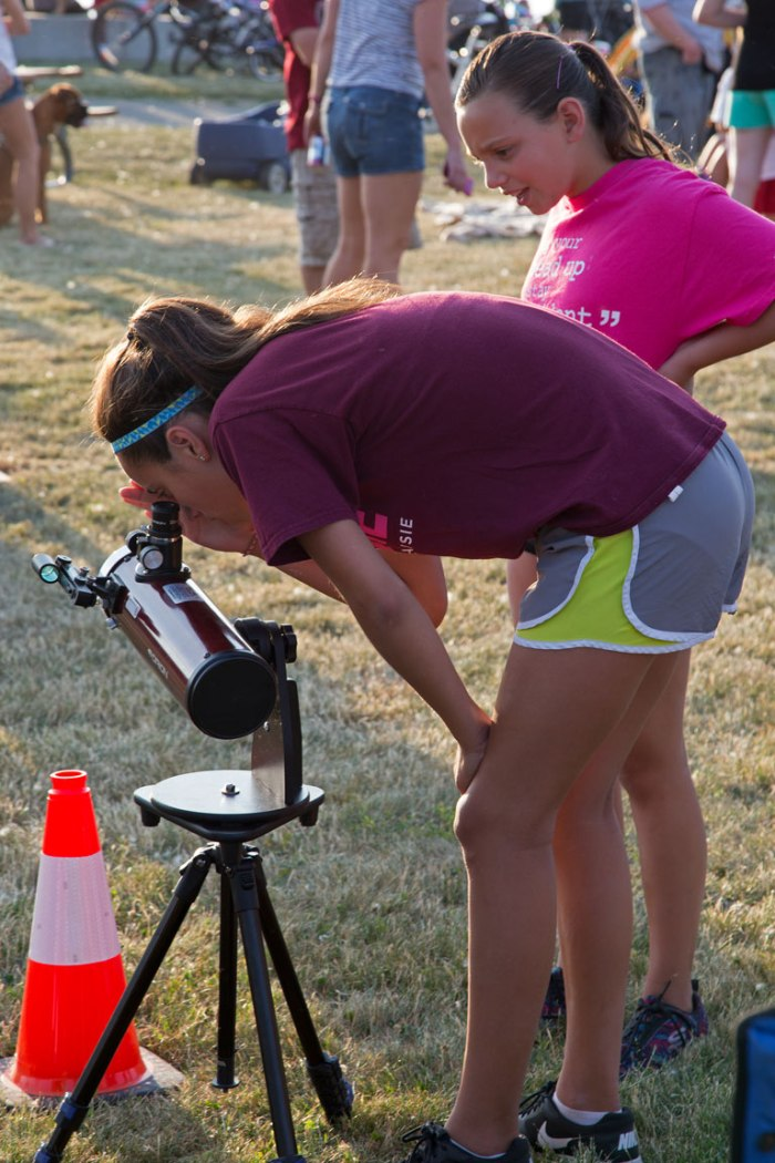 Photo: Two young ladies view the Sun through a rather short telescope. Photo by James Guilford.