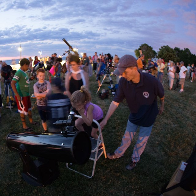 Photo: A Dobsonian light-bucket affords views of Saturn to a little girl. Photo by James Guilford.