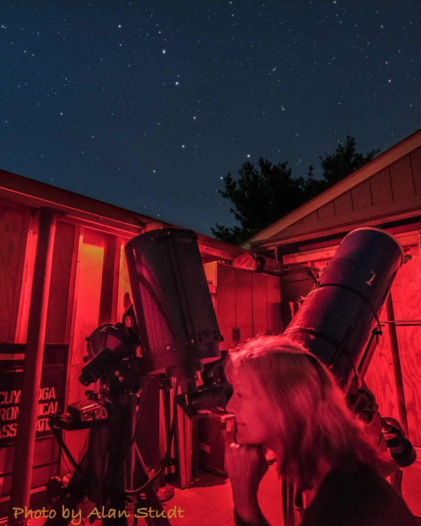 Photo: Woman using telescope in red-lit observatory under starry sky.