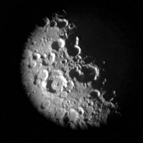 Photo: Craters on the Moon's Terminator. An iPhone photo taken through a telescope at 600X. Converted to monochrome.  Photo Credit: Lowan Laws.
