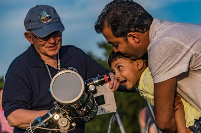 Photo: Child gets support looking through telescope. Photo by Alan Studt.