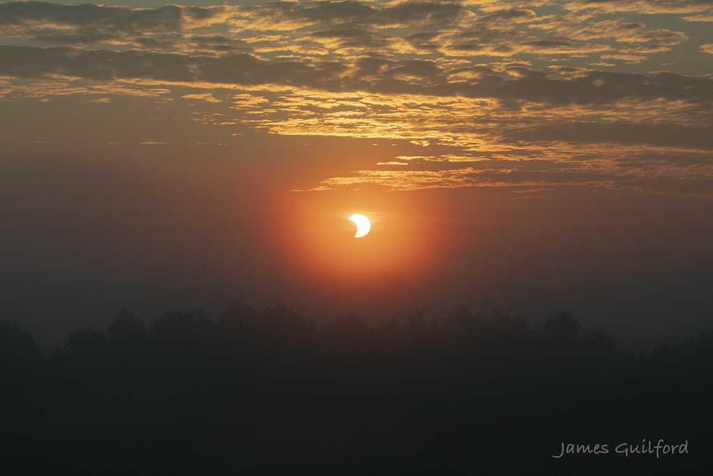 Eclipsed Sun rising through morning fog in rural Medina County. by James Guilford